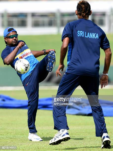 Sri Lankan cricket captain Rangana Herath play football as teammate Suranga Lakmal looks on during a practice session at Galle International Cricket...