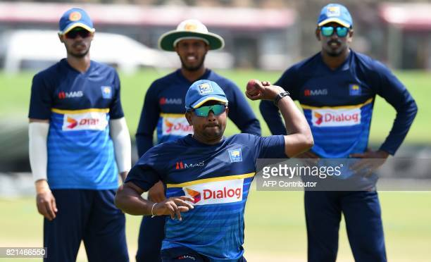 Sri Lankan cricket captain Rangana Herath throws a ball as teammates look on during a practice session at Galle International Cricket Stadium in...