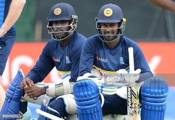 Sri Lankan cricket captain Upul Tharanga and Angelo Mathews watch other players during a practice session at the Rangiri Dambulla International...