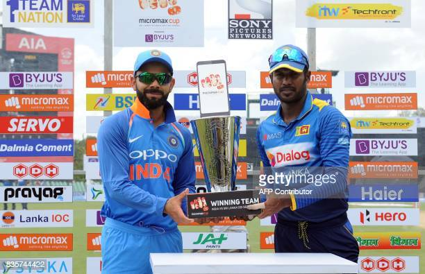 Sri Lankan cricket captain Upul Tharanga and Indian cricket captain Virat Kohli pose for photographers with the One Day International trophy before...