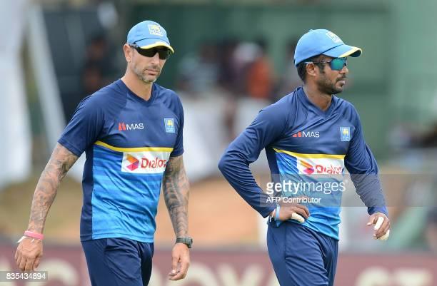 Sri Lankan cricket coach Nic Pothas walks with captain Upul Tharanga upon their arrival during a practice session at the Rangiri Dambulla...
