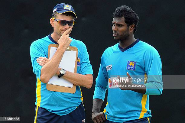 Sri Lankan cricket team captain Angelo Mathews speaks with team coach Graham Ford during a practice session at the Pallekele International Cricket...