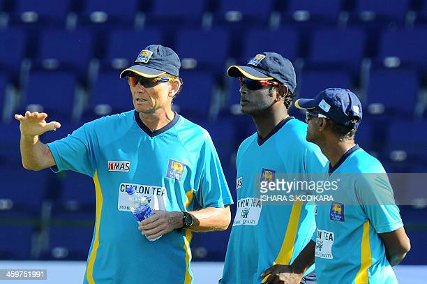 Sri Lankan cricket team captain Angelo Mathews speaks with team coach Graham Ford during a practice session at the Sheikh Zayed Stadium in Abu Dhabi...