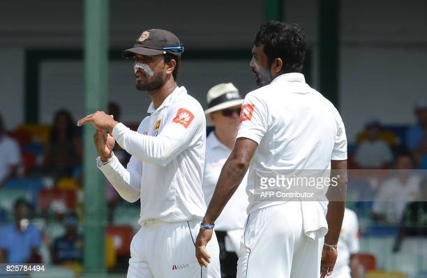 Sri Lankan cricket team captain Dinesh Chandimal signals for a third umpire review as teammate Dilruwan Perera look on during the first day of the...