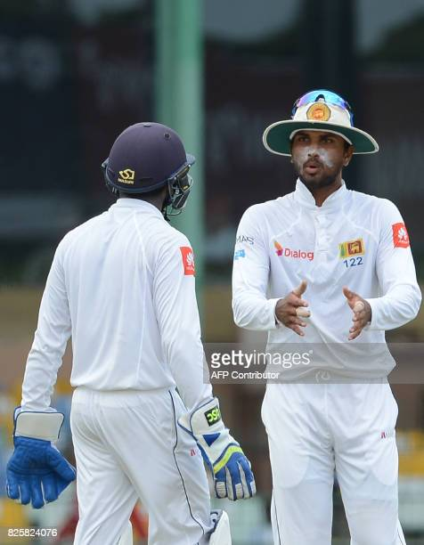 Sri Lankan cricket team captain Dinesh Chandimal speaks with wicketkeeper Niroshan Dickwella during the first day of the second Test match between...
