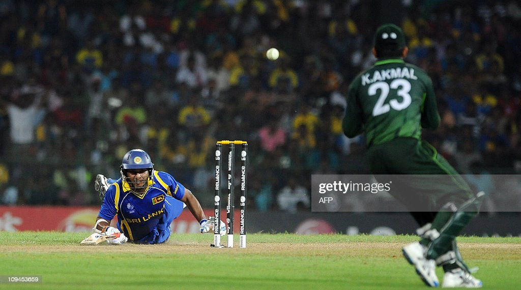Sri Lankan cricket team captain Kumar Sangakkara (L) dives towards the crease to avoid a runout by Pakistan cricketer Kamran Akmal (R) during the Group A match in the World Cup Cricket tournament between Sri Lanka and Pakistan at The R. Premadasa Stadium in Colombo on February 26, 2011. Sri Lanka are 177 runs for the loss of five wickets after 39 overs as they chase the Pakistan score of 277. AFP PHOTO/Ishara S. KODIKARA