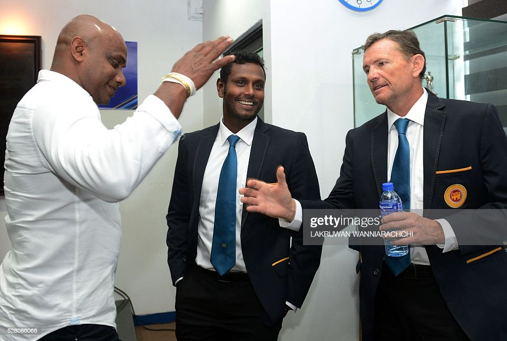 Sri Lankan cricket team head coach Graham Ford (R) shakes hands with former skipper Sanath Jayasuriya (L) as captain Angelo Mathews looks on at a press conference as the team prepare to leave for their forthcoming England tour in Colombo on May 4, 2016. / AFP / LAKRUWAN