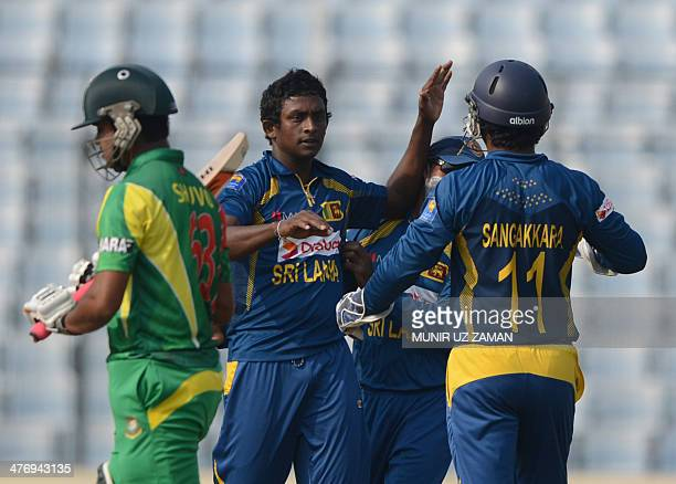 Sri Lankan cricketer Ajantha Mendis celebrates with his teammate Kumar Sangakkara after the dismissal of Bangladeshi batsman Shamsur Rahman during...