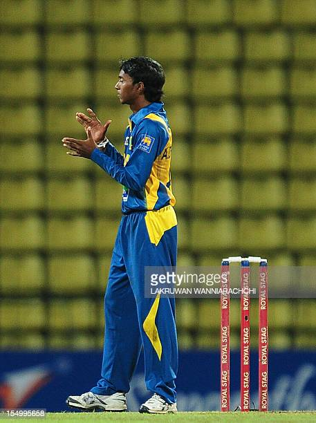 Sri Lankan cricketer Akila Dananjaya celebrates after he dismissed New Zealand's cricketer Andrew Ellis during the oneoff Twenty20 international...