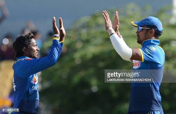 Sri Lankan cricketer Akila Dananjaya celebrates with teammate Danushka Gunathilaka after he dismissed Zimbabwe cricketer Tarisai Musakanda during the...