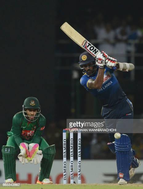 Sri Lankan cricketer Chamara Kapugedera is watched by Bangladesh wicketkeeper Mushfiqur Rahim as he plays a shot during the second T20 international...