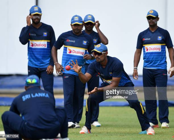 Sri Lankan cricketer Danushka Gunathilaka catches the ball as teammates looks on during a practice session at the R Premadasa Cricket Stadium in...