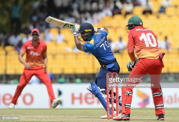 Sri Lankan cricketer Danushka Gunathilaka is watched by Zimbabwe wicketkeeper Peter Moor as he plays a shot during the fourth oneday international...