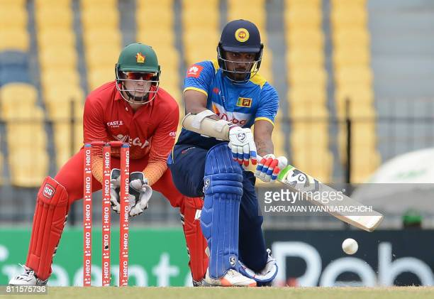 Sri Lankan cricketer Danushka Gunathilaka is watched by Zimbabwe wicketkeeper Peter Moor as he plays a shot during the fifth oneday international...