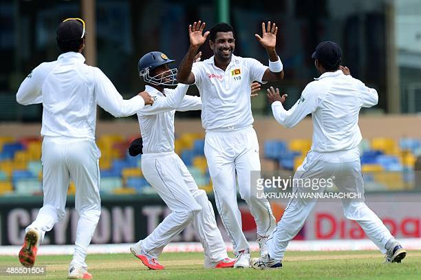 Sri Lankan cricketer Dhammika Prasad celebrates with teammates after he dismissed Indian cricketer Lokesh Rahul during the opening day of their third...