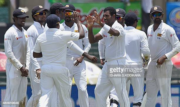 Sri Lankan cricketer Dhammika Prasad celebrates with teammates after he dismissed Indian cricketer Rohit Sharma during the second day of the third...