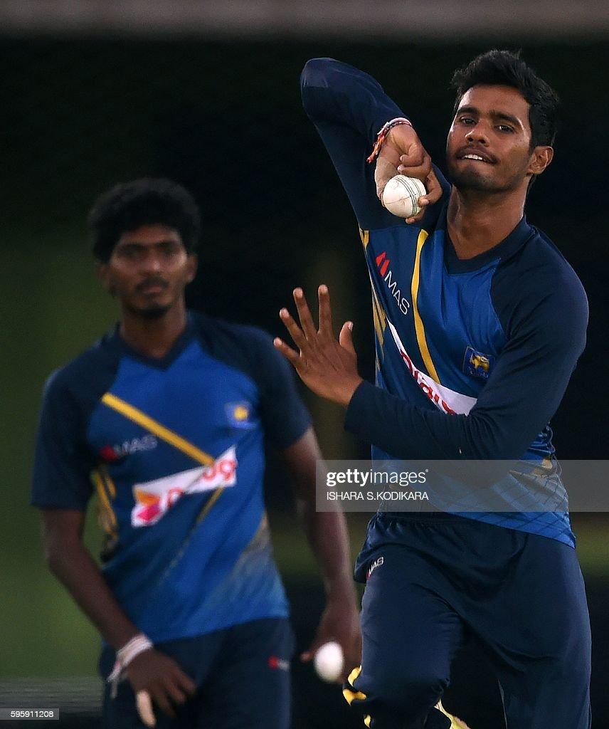 Sri Lankan cricketer Dhananjaya de Silva delivers a ball as teammate Lakshan Sandakan looks on during a practice session at The Rangiri Dambulla...
