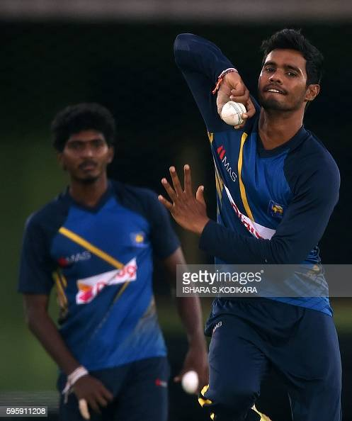 Sri Lankan cricketer Dhananjaya de Silva delivers a ball as teammate Lakshan Sandakan looks on during a practice session at The Rangiri Dambulla...