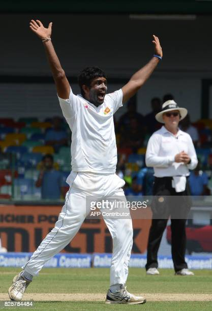 Sri Lankan cricketer Dilruwan Perera celebrates after dismissing India's Shikhar Dhawan during the first day of the second Test match between Sri...