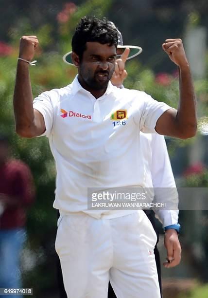 Sri Lankan cricketer Dilruwan Perera celebrates after he dismissed Bangladesh batsman Mehedi Hasan during the third day of the opening Test cricket...