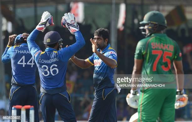 Sri Lankan cricketer Dilruwan Perera celebrates with his teammates as the dismissed Bangladesh cricketer Shakib Al Hasan looks on during the third...