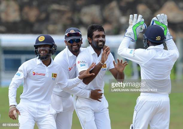 Sri Lankan cricketer Dilruwan Perera celebrates with his teammates after he dismissed Bangladesh cricketer Tamim Iqbal during the final day of the...