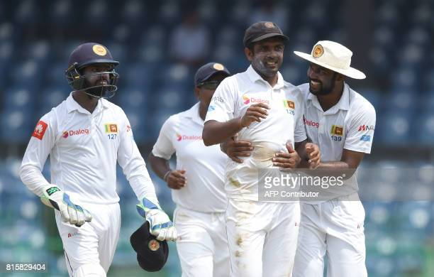 Sri Lankan cricketer Dilruwan Perera celebrates with his teammates after he dismissed Zimbabwe cricketer Malcolm Waller during the fourth day of the...