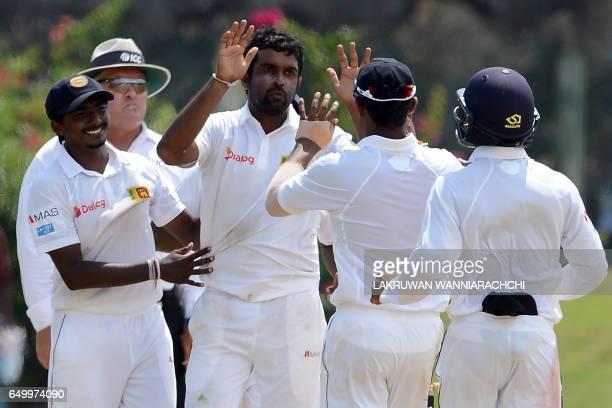 Sri Lankan cricketer Dilruwan Perera celebrates with teammates after he dismissed Bangladesh batsman Mehedi Hasan during the third day of the opening...