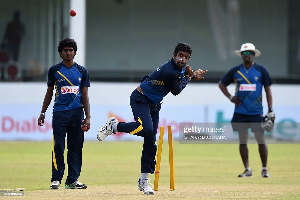 Sri Lankan cricketer Dilruwan Perera delivers a ball as Lakshan Sandakan looks on during a practice session at The Galle International Cricket...