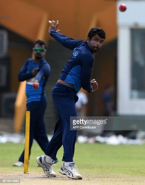 Sri Lankan cricketer Dilruwan Perera delivers a ball as Malinda Pushpakumara looks on during a practice session at Galle International Cricket...