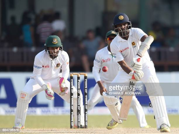 Sri Lankan cricketer Dilruwan Perera plays a shot as Bangladesh captain and wicketkeeper Mushfiqur Rahim looks on during the fourth day of the second...