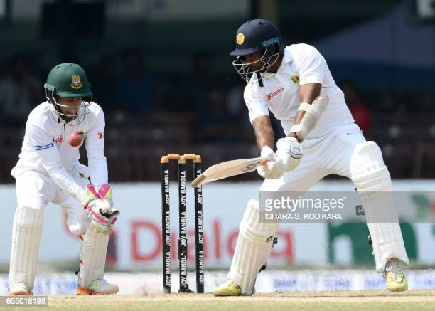 Sri Lankan cricketer Dilruwan Perera plays a shot as Bangladesh captain and wicketkeeper Mushfiqur Rahim looks on during the fifth and final day of...