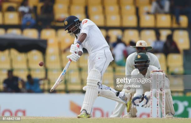Sri Lankan cricketer Dilruwan Perera plays a shot as Zimbabwe's wicketkeeper Regis Chakabva looks on during the Second day of the only oneoff Test...