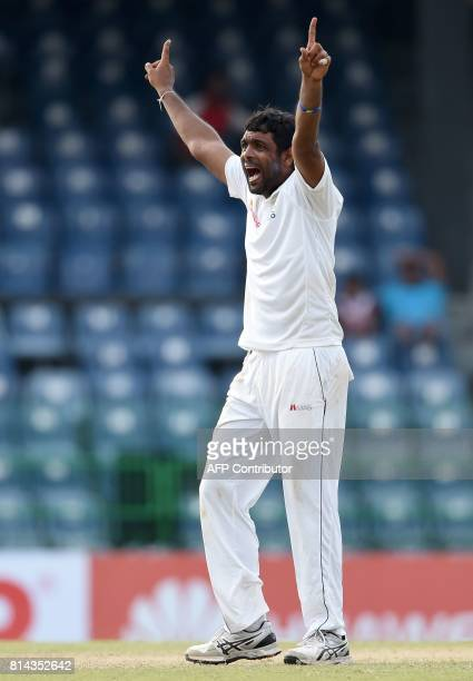 Sri Lankan cricketer Dilruwan Perera successfully appeals for a Leg Before Wicket decision against Zimbabwe's cricketer Craig Ervine during the first...