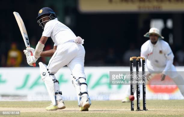 Sri Lankan cricketer Dilruwan Perera watches the ball after playing a shot during the fifth and final day of the second and final Test cricket match...