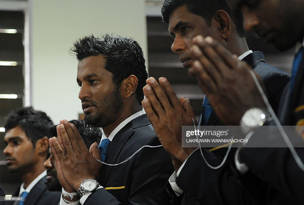 Sri Lankan cricketer Dimuth Karunaratne (2L) and teammates look on as Buddhist monks chant prayers for their success as they prepare to leave for their forthcoming England tour during a ceremony in Colombo on May 4, 2016. / AFP / LAKRUWAN