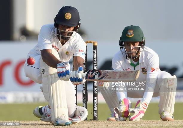 Sri Lankan cricketer Dimuth Karunaratne plays a shot as Bangladesh wicketkeeper Mushfiqur Rahim looks on during the third day of the second and final...