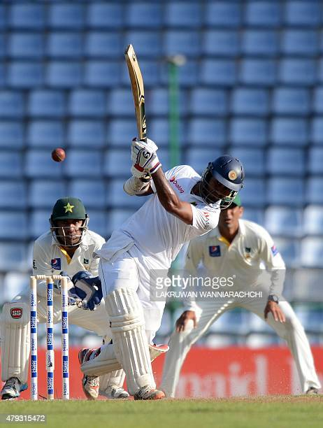 Sri Lankan cricketer Dimuth Karunaratne plays a shot as wicketkeeper Sarfraz Ahmed and Younis Khan look on during the opening day of the third and...