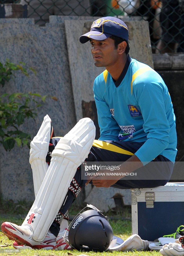 Sri Lankan cricketer Dimuth Karunaratne puts on his leg pads for a practice session at the Galle International Cricket Stadium in Galle on March 7, 2013. Sri Lanka will play two Tests, three one-dayers and one Twenty20 cricket matches against Bangladesh, with the first Test to start March 8 in Galle.