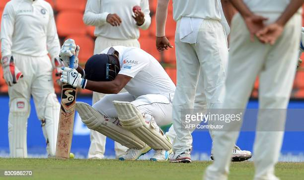 Sri Lankan cricketer Dimuth Karunaratne reacts after been hit on it off the ball of unseen Indian cricketer Mohammed Shami during the second day of...