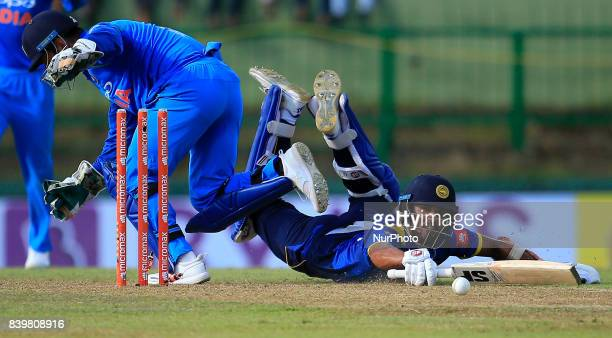 Sri Lankan cricketer Dinesh Chandimal dives in as India's MS Dhoni removes the bails in an unsuccessful runout opportunity during the 3rd One Day...