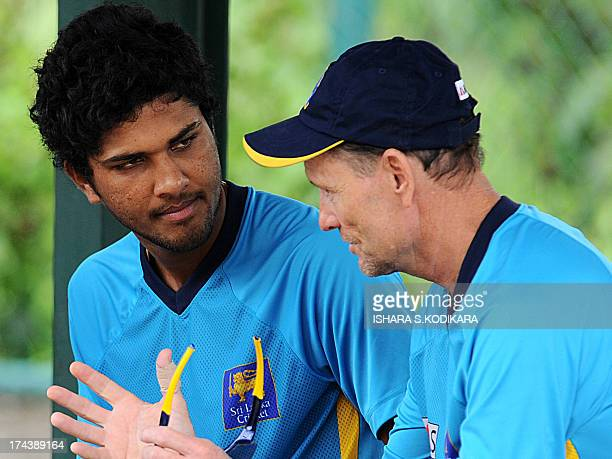 Sri Lankan cricketer Dinesh Chandimal listens to team coach Graham Ford during a practice session at the Pallekele International Cricket Stadium in...