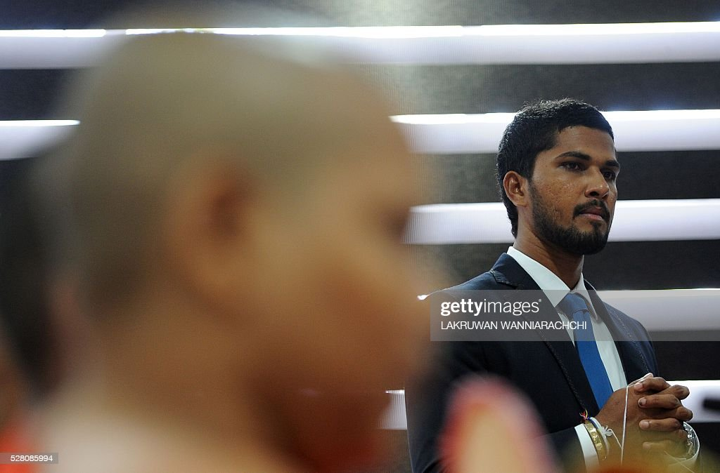 Sri Lankan cricketer Dinesh Chandimal looks on as Buddhist monks chant prayers for success as the Sri Lankan cricket team prepare to leave for their forthcoming England tour during a ceremony in Colombo on May 4, 2016. / AFP / LAKRUWAN