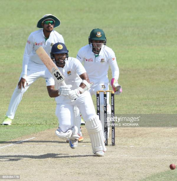 Sri Lankan cricketer Dinesh Chandimal plays a shot as Bangladesh captain Mushfiqur Rahim looks on during the first day of the second and final Test...