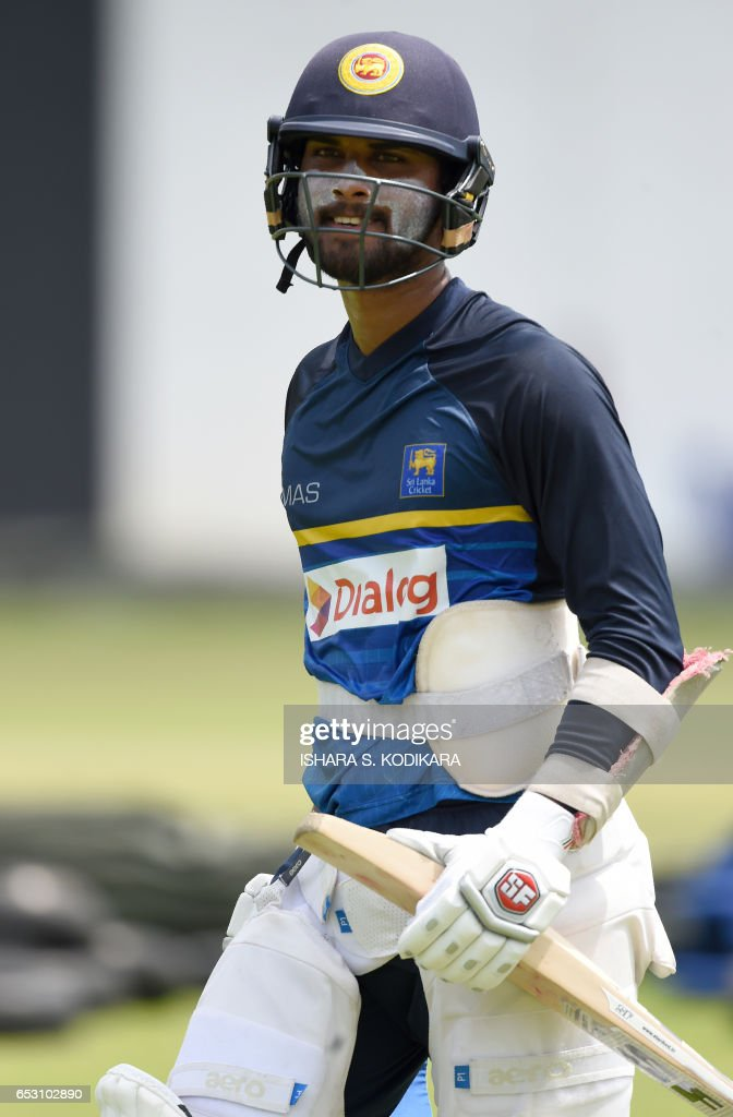 Sri Lankan cricketer Dinesh Chandimal walks with his equipment during a practice session at The P. Sara Oval Cricket Stadium in Colombo on March 14, 2017. Bangladesh play their 100th Test on March 15, against Sri Lanka at The P. Sara Oval Cricket Stadium in Colombo. / AFP PHOTO / Ishara S. KODIKARA
