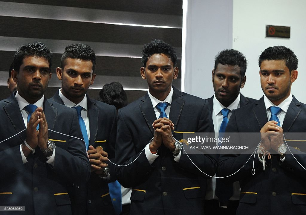 Sri Lankan cricketer Dushmantha Chameera (C) and teammates look on as Buddhist monks chant prayers for their success as they prepare to leave for their forthcoming England tour during a ceremony in Colombo on May 4, 2016. / AFP / LAKRUWAN