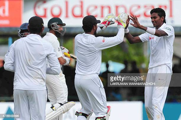 Sri Lankan cricketer Dushmantha Chameera celebrates with teammates the wicket of Pakistan cricketer Junaid Khan during the fourth day of the second...