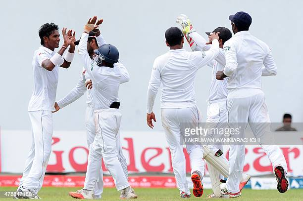 Sri Lankan cricketer Dushmantha Chameera is congratulated by teammates on the dismissal of Pakistan cricketer Asad Shafiq during the fourth day of...