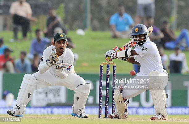 Sri Lankan cricketer Kaushal Silva is watched by Pakistan wicketkeeper Sarfraz Ahmed as he plays a shot during the second day of the opening Test...