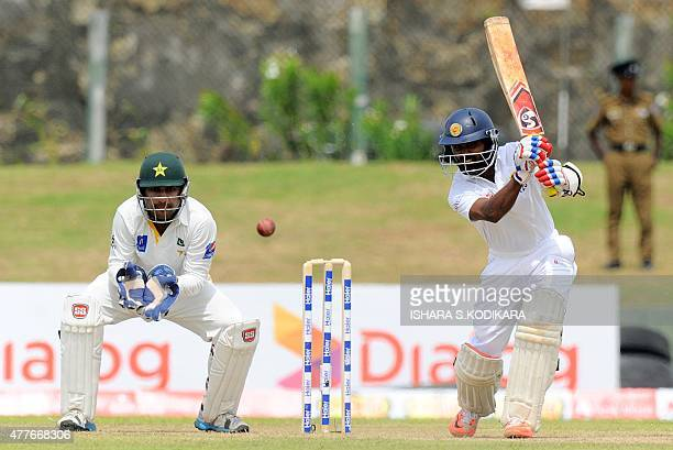 Sri Lankan cricketer Kaushal Silva plays a shot as Pakistan wicketkeeper Sarfraz Ahmed looks on during the third day of the opening Test match...